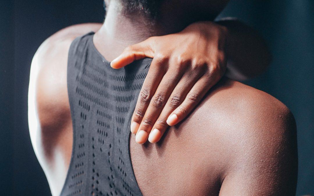 woman rubbing her shoulder in pain
